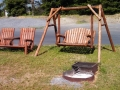 Adirondak-style chairs and swing on end of row campsites